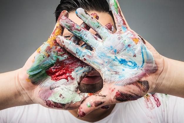 A mão de um artista pintor é coberta com tinta