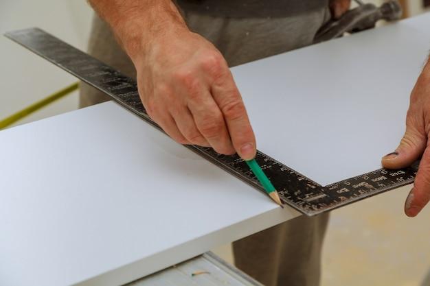 A mão de um carpinteiro mede a distância usando o quadrado e as marcas de um construtor
