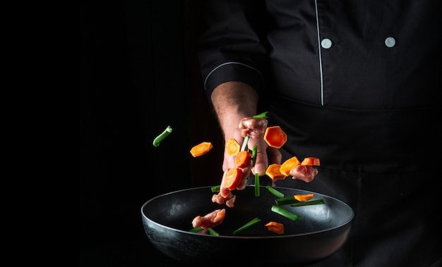 A mão de um chef profissional joga pedaços de vegetais e carne em uma frigideira