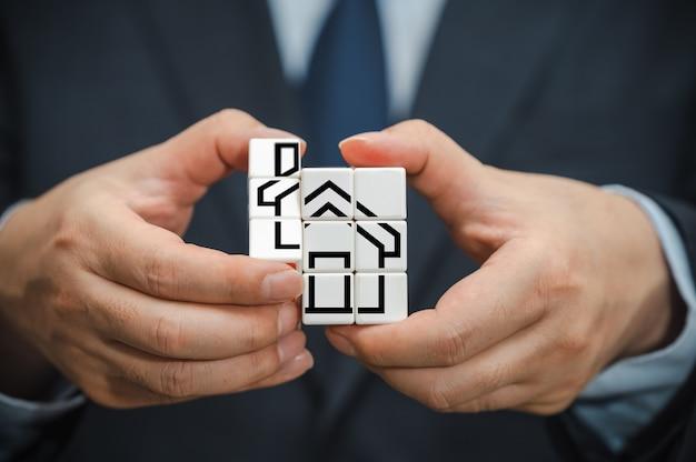 A mão de um empresário segurando um cubo com vista para o ícone da casa.