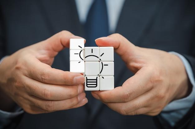 A mão de um empresário segurando um cubo com vista para o ícone de lâmpada.