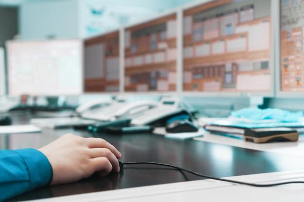 A mão de um engenheiro segura um mouse de pc e controla o trabalho de geração de energia elétrica.