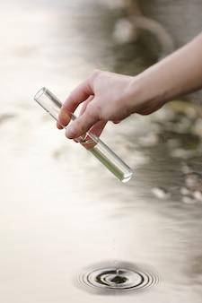A mão de um especialista atrai água para um balão de um rio