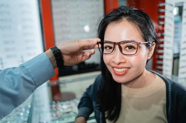 A mão de um funcionário está ajudando a colocar um par de óculos que uma mulher que fez um exame de vista escolheu em uma clínica de olhos