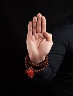 A mão de um homem adulto mostra o mudra de abhayaprada no gesto protetor, escuro