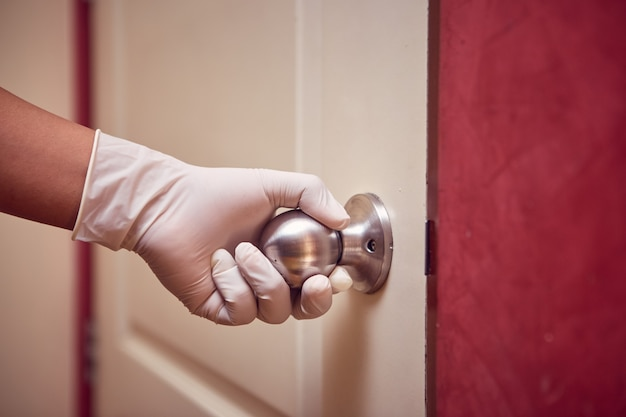A mão de um homem com luva de látex abre a porta tocando na maçaneta