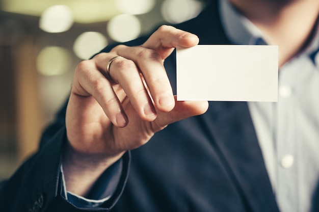 A mão de um homem com um cartão de visita.