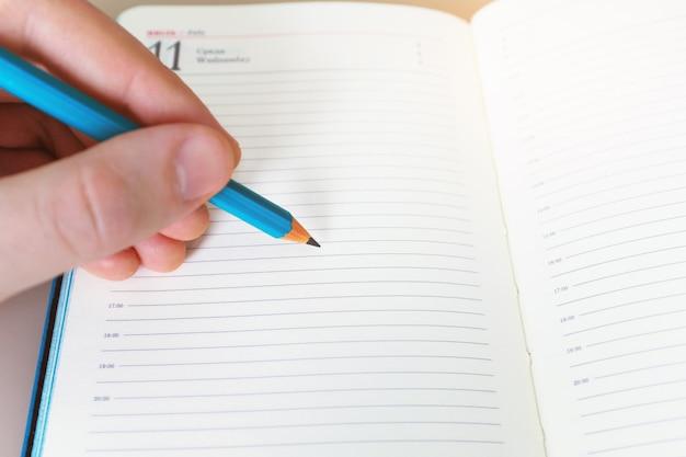 A mão de um homem com um lápis escreve algo em um caderno branco em uma folha em branco.