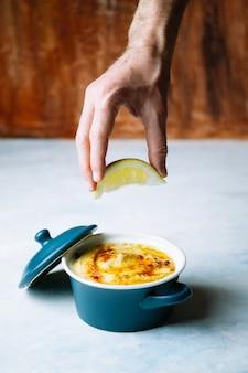 A mão de um homem com um pedaço de limão para derramar seu suco em um prato de delicioso homus com azeite e páprica. conceito de comida