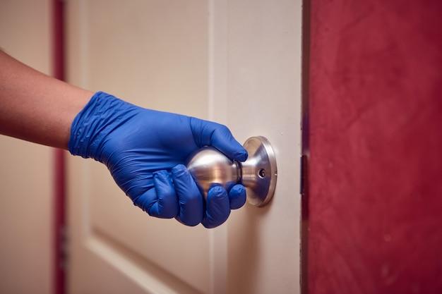 A mão de um homem com uma luva de nitrila abre a porta tocando na maçaneta