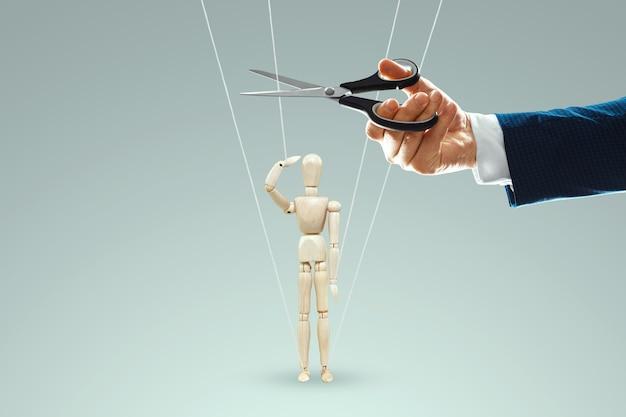 A mão de um homem corta os fios entre o titereiro e o fantoche com uma tesoura. o conceito de libertação da escravidão, liberdade, governo paralelo, conspiração mundial, manipulação, controle.