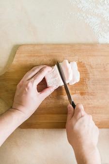 A mão de um homem corta os pedaços de gordura