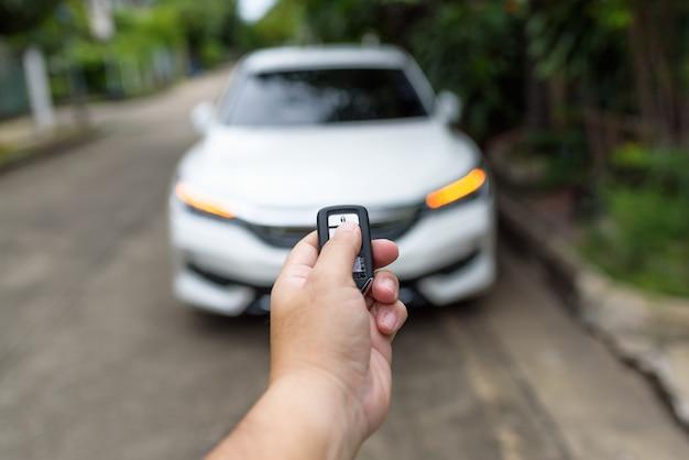 A mão de um homem está pressionando o controle remoto para trancar ou destrancar a porta do carro.