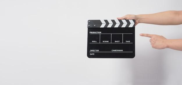 A mão de um homem está segurando uma claquete preta ou uma tela de cinema. é usado na produção de vídeo ou na indústria do cinema. é o fundo branco.