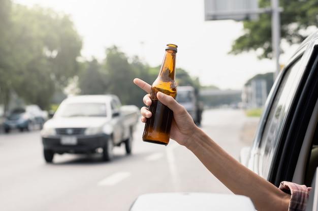 A mão de um homem está segurando uma jarra de álcool.