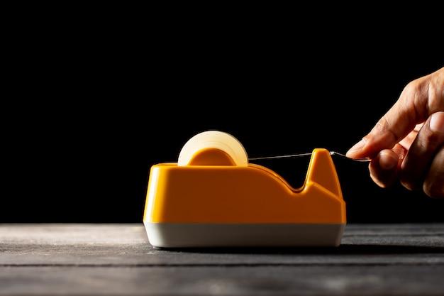A mão de um homem está usando um cortador de fita amarela.