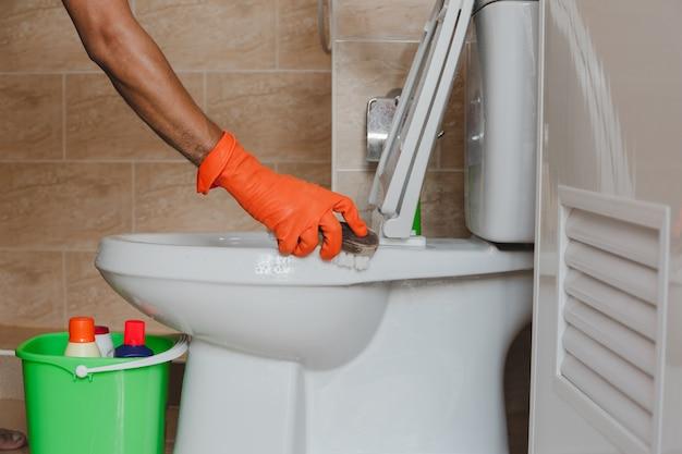 A mão de um homem que veste luvas de borracha alaranjadas é usada para converter o polimento a um toalete.