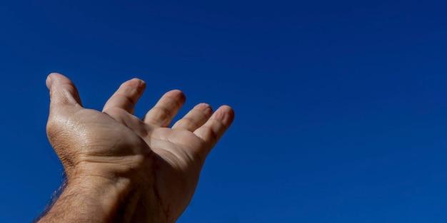 A mão de um homem se aproxima do céu azul. símbolo de fé