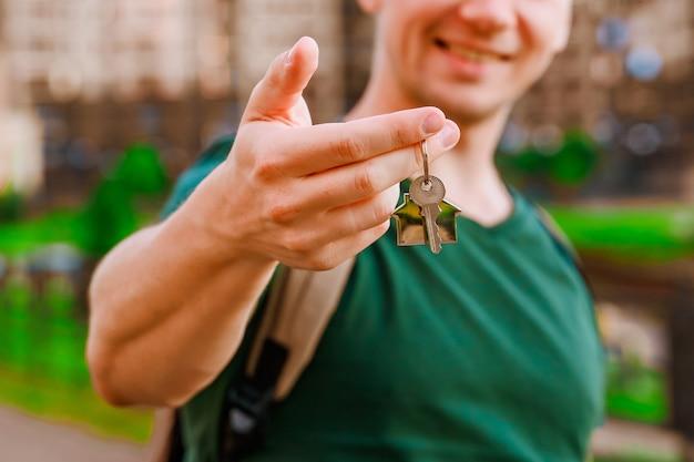 A mão de um homem segura as chaves de uma nova casa no contexto de edifícios altos