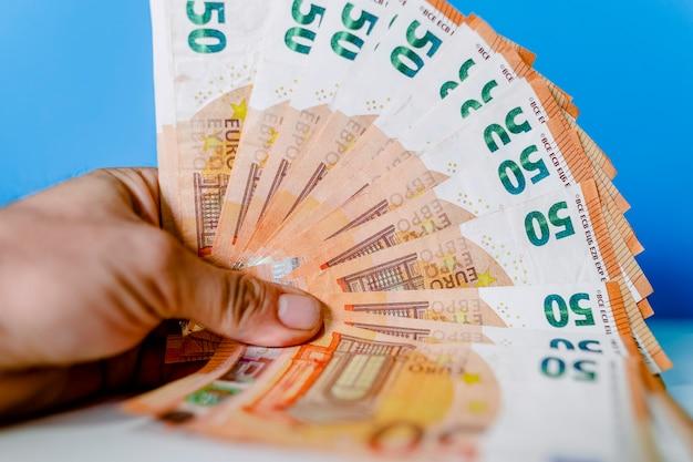 A mão de um homem segura muitas notas de euro