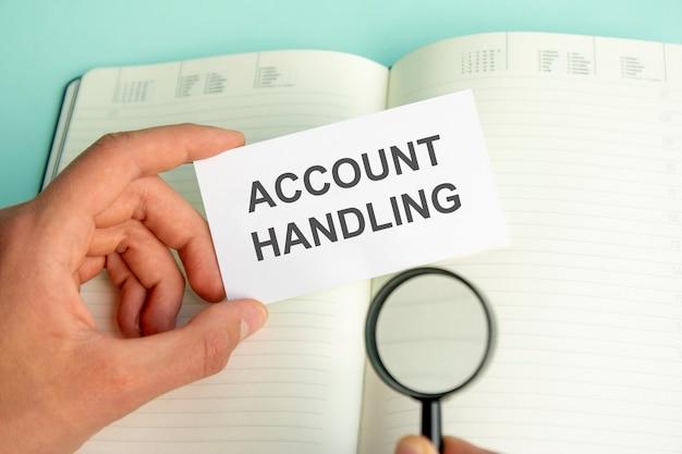 A mão de um homem segura um cartão branco com o texto gerenciamento de contas acima de um caderno de papel aberto e uma lupa em uma moldura preta, conceito de negócio