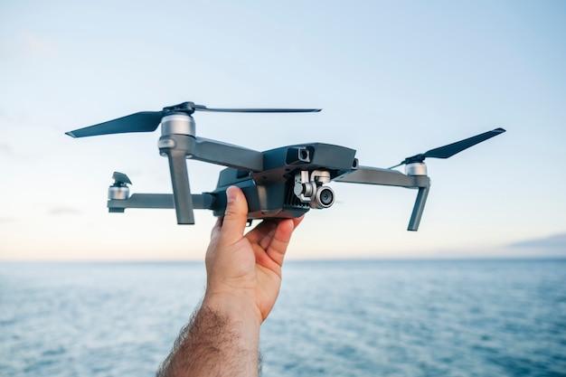 A mão de um homem segura um drone antes de iniciar a decolagem