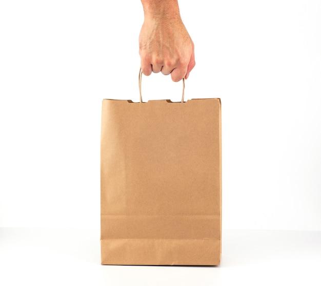 A mão de um homem segura um saco de papel kraft