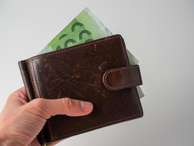 A mão de um homem segura uma carteira de couro marrom com notas de 100 euros saindo dela em um fundo branco. o conceito de dinheiro, riqueza, riqueza