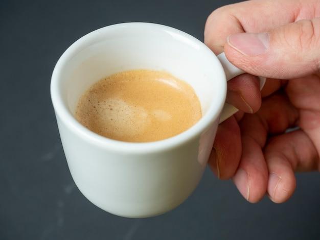 A mão de um homem segura uma xícara de café expresso acabado de fazer sobre um fundo escuro. espuma castanha. uma bebida revigorante. vista do topo