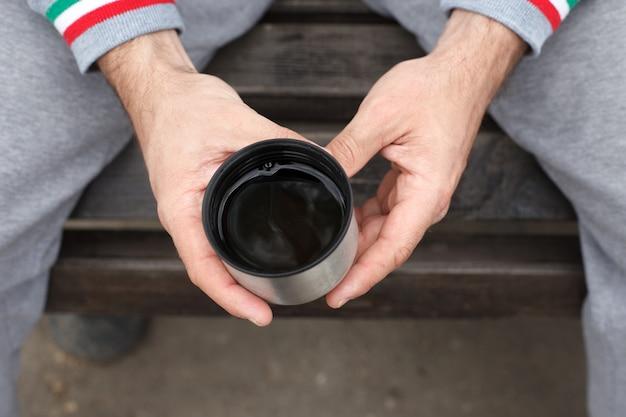 A mão de um homem segura uma xícara de chá ou café de uma garrafa térmica.