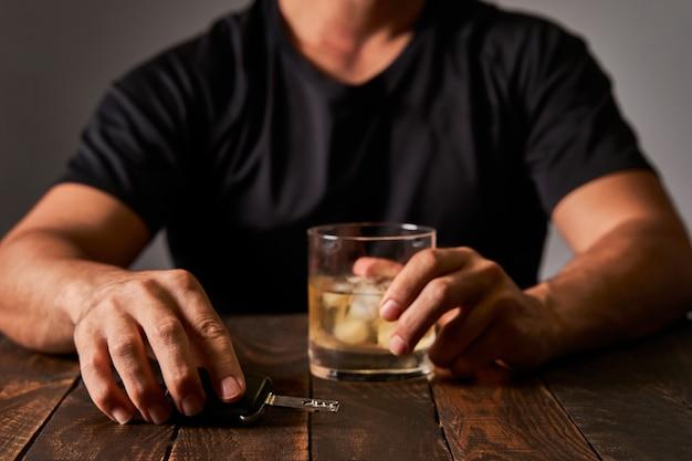 A mão de um homem segurando um copo de álcool e uma chave de carro. conceito de alcoolismo e acidentes de trânsito causados por álcool.