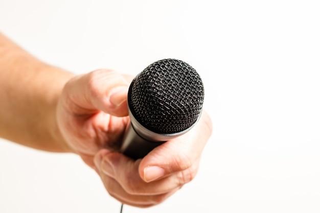 A mão de um homem segurando um microfone preto. conceito de comunicação, entrevistas, diálogos virtuais.