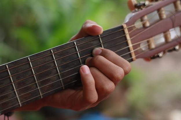 A mão de um homem tocando violão e música