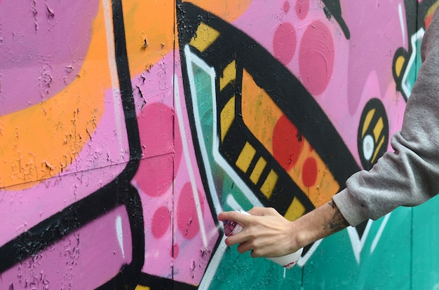 A mão de um indivíduo novo em um hoodie cinzento pinta grafittis na cor-de-rosa e