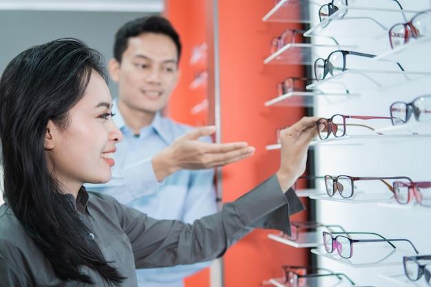 A mão de um médico está mostrando um par de óculos recomendado para uma paciente que foi submetida a um exame em uma clínica de olhos