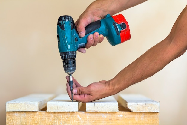 A mão de um trabalhador parafusa um parafuso em uma placa de madeira com uma chave de fenda sem fio