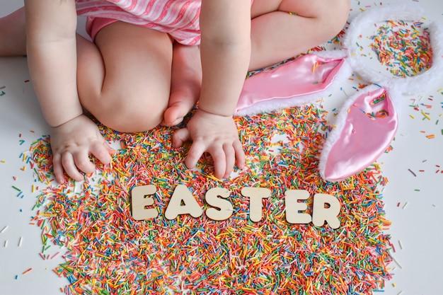 A mão de uma criança alcança a palavra páscoa. polvilhe para produtos de confeitaria. páscoa