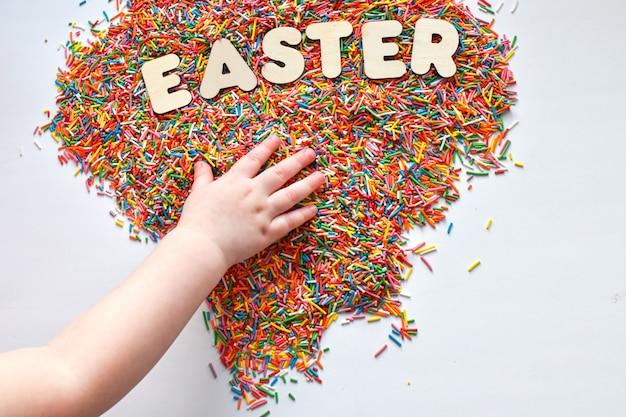 A mão de uma criança alcança a palavra páscoa. polvilhe para produtos de confeitaria.