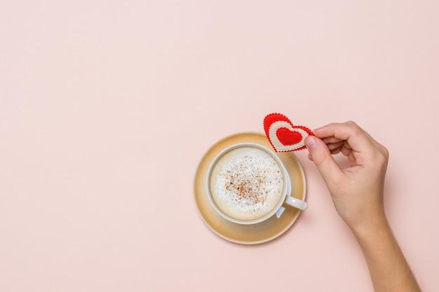 A mão de uma criança segura um coração vermelho sobre uma xícara de café com canela