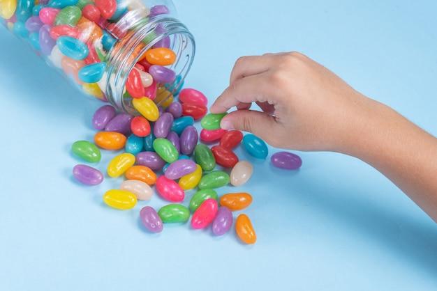A mão de uma criança segurando vários jelly beans sobre a superfície azul