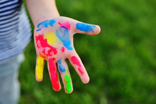 A mão de uma criança sujada no dedo colorido pinta o close-up em um fundo da grama.