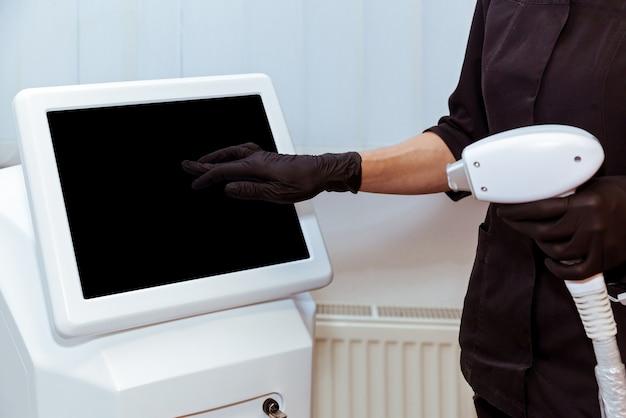A mão de uma esteticista em uma luva pressiona o monitor em uma máquina a laser moderna h