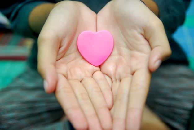 A mão de uma garota segurando um coração rosa, conceito de amor