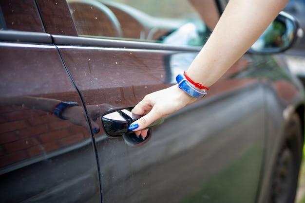 A mão de uma mulher abre a porta de um carro preto