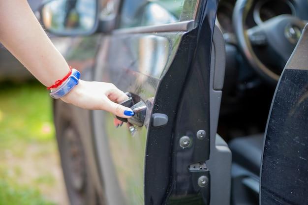 A mão de uma mulher abre a porta do motorista de um carro preto