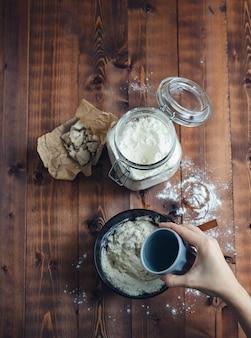 A mão de uma mulher adicionando água a uma tigela de farinha para fazer massa fermentada.