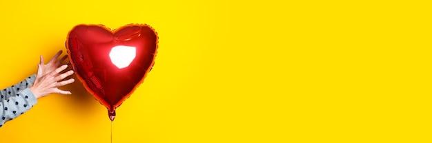 A mão de uma mulher alcança o balão de ar em forma de coração em um fundo amarelo. bandeira.