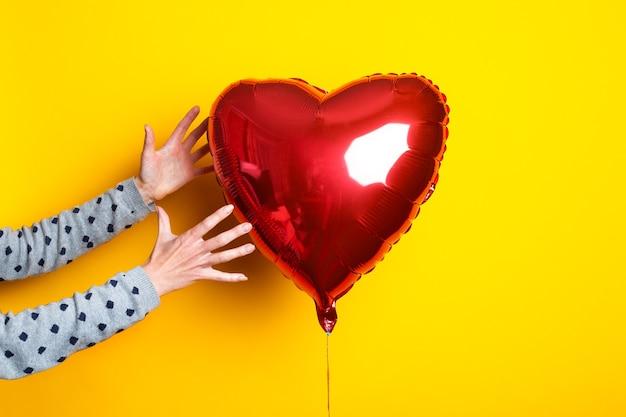 A mão de uma mulher alcança o balão de ar em forma de coração em um fundo amarelo.