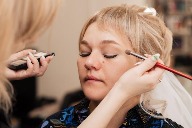 A mão de uma mulher aplica e sombreia a sombra com um pincel de maquiagem.
