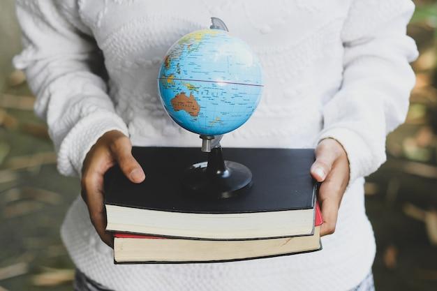 A mão de uma mulher asiática segura uma pilha de livros e um globo
